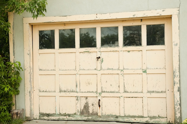 garage door in need of repair and painting as is the concrete entrance